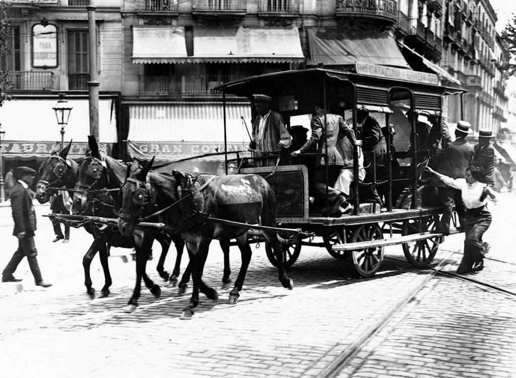 Un carruatge transporta persones a la ciutat de Barcelona al segle XIX